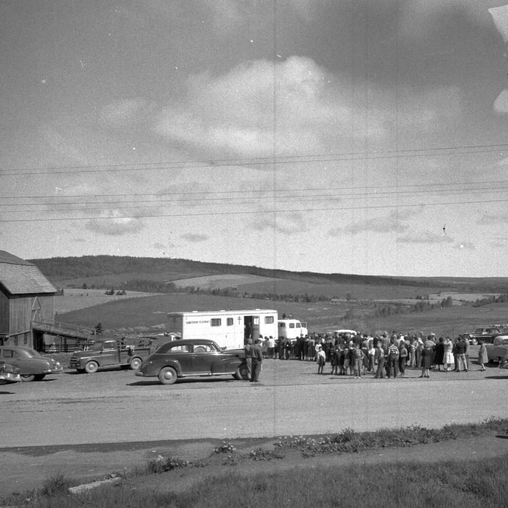 Une photographie en noir et blanc d'une file de personnes devant un champ voulant entrer dans une roulotte où étaient prises des radiographies.