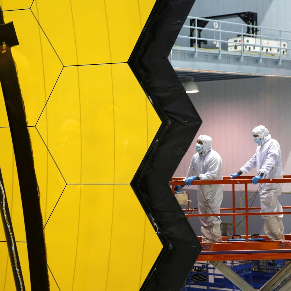 Des travailleurs en combinaison près d'un télescope spatial.