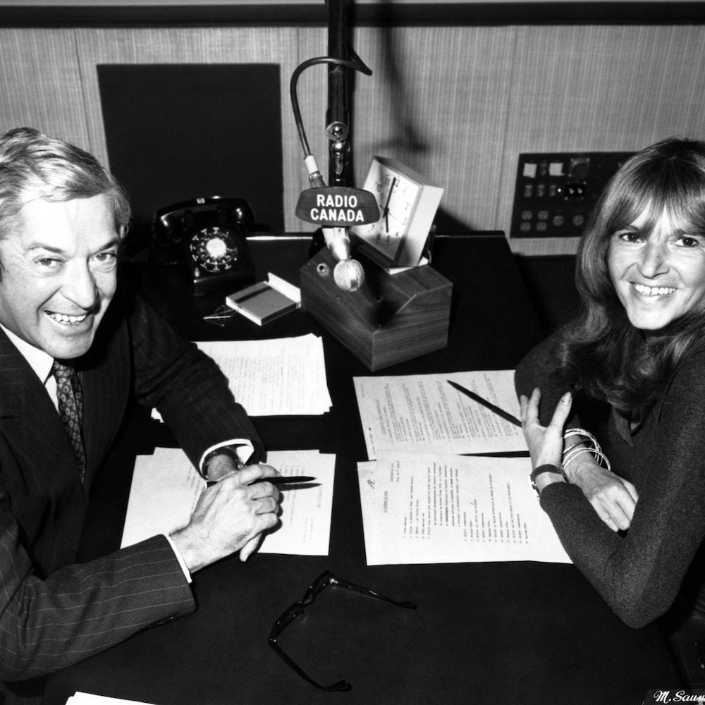 Colette Devlin et Fernand Seguin sont assis face à face à une table, un micro est suspendu entre les deux.