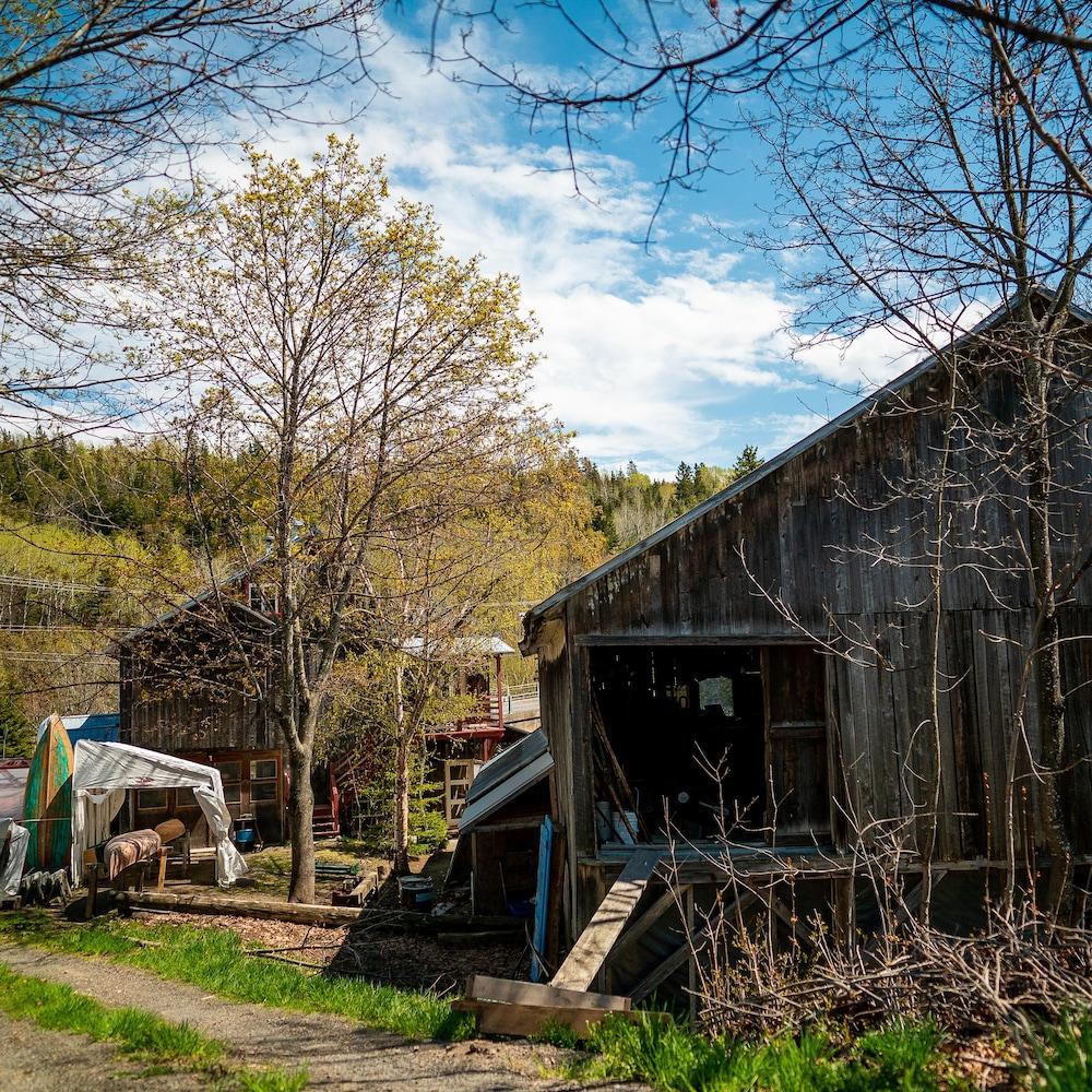 Un ancien moulin servant d'atelier et des chaloupes entreposées à l'extérieur.