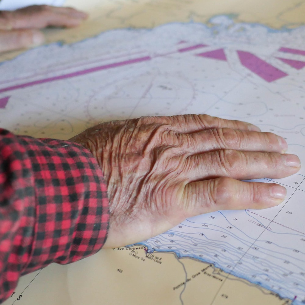 Les mains de Daniel St-Pierre déposées sur une carte marine.