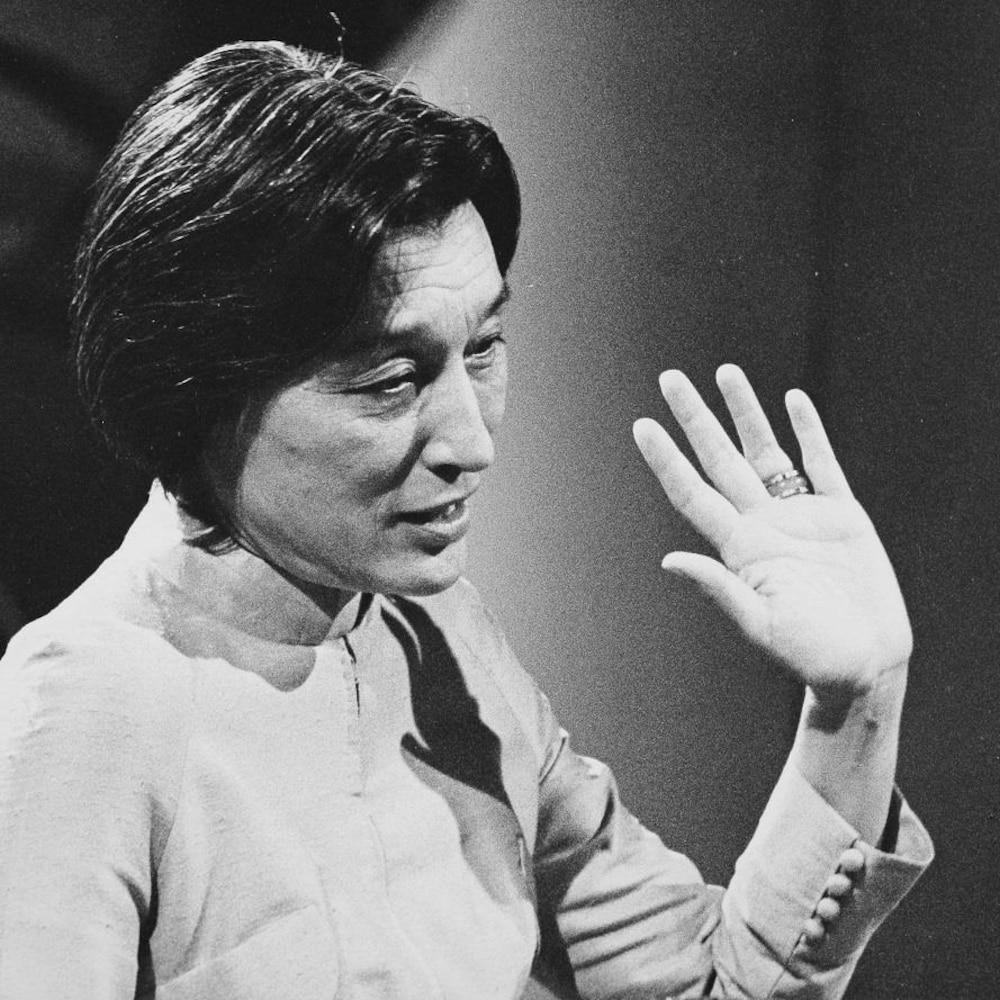 Dans un studio de télévision, l'écrivaine Han Suyin, levant le bras lors d'une entrevue. Un micro de table est posé devant elle.