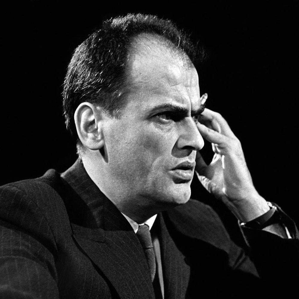 Jean-Paul Desbiens est assis à une table devant un micro et une main tenant une cigarette est appuyée contre sa tempe.
