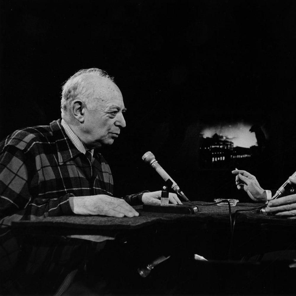 Dans un studio de télévision, le photographe Brassaï discute avec l'animateur Fernand Seguin. Deux microphones sont posés sur le pupitre devant eux.