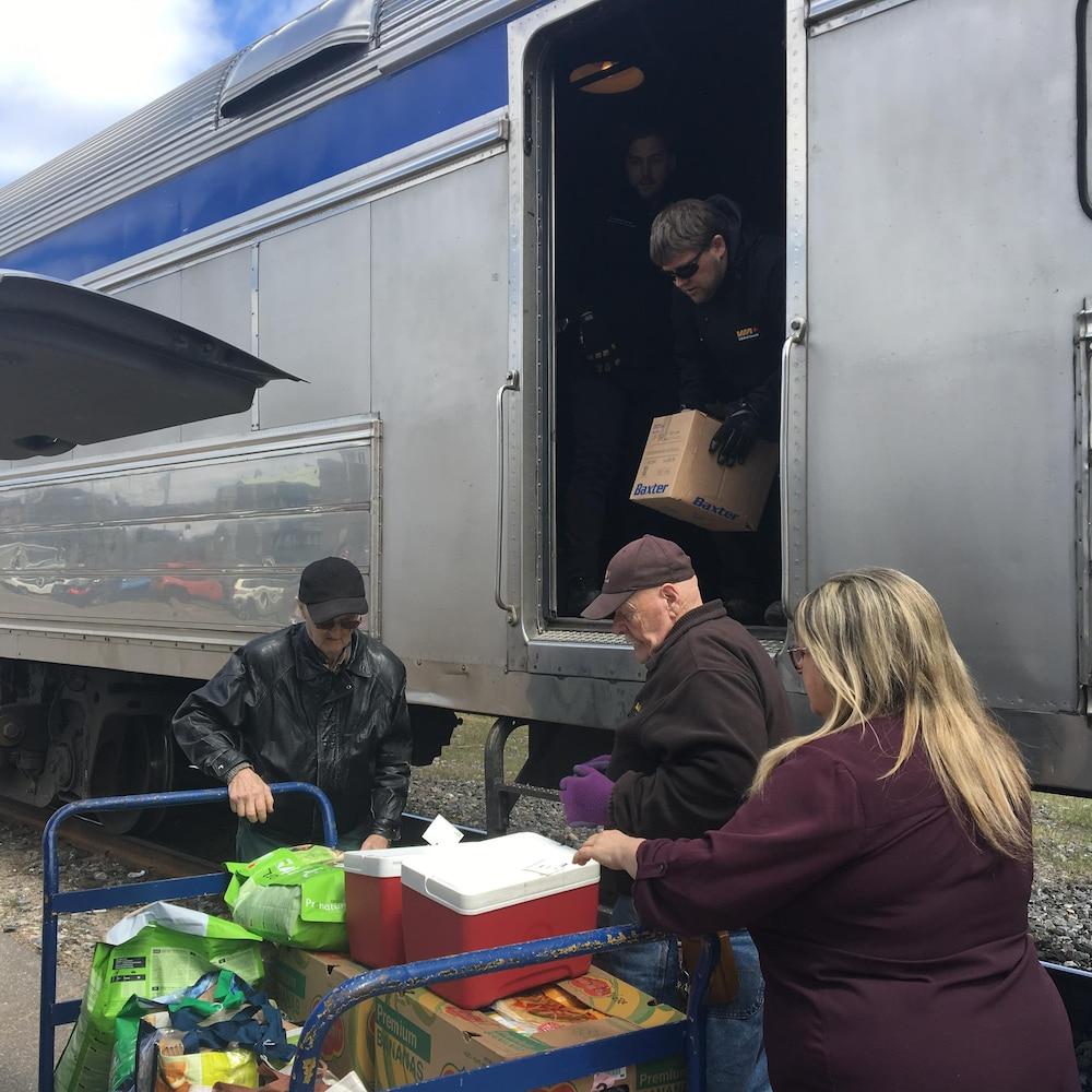 Des gens déchargent de la marchandise du train.