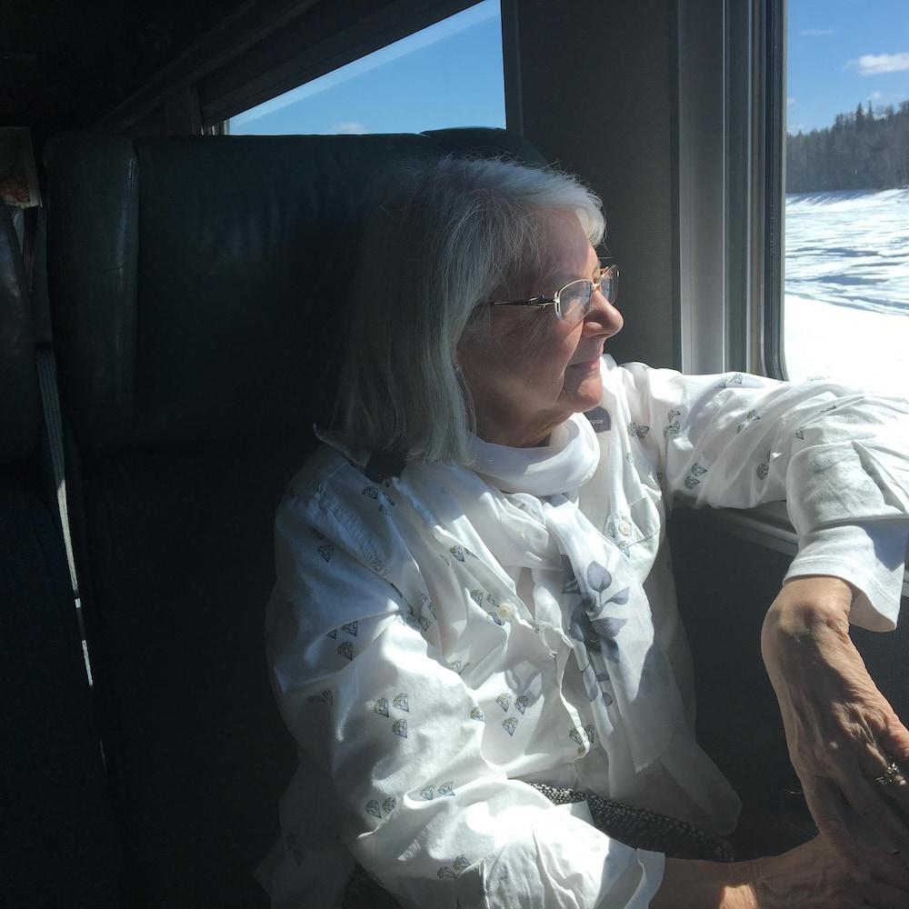 Élise Parent qui regarde par la fenêtre du train.