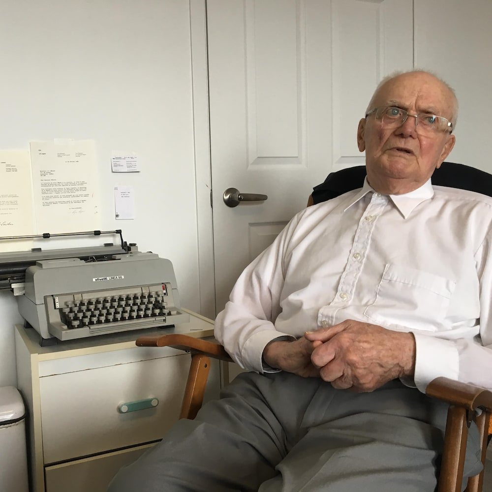 Sylvio Ménard assis à côté d'une vieille dactylo.