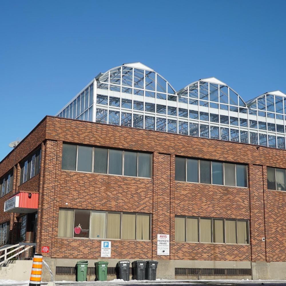 Un édifice de deux étages avec une serre sur le toit.