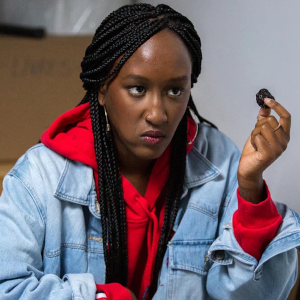 Une jeune femme noire porte un cotton ouaté rouge et tient un pruneau dans sa main. Elle a un regard blasé.