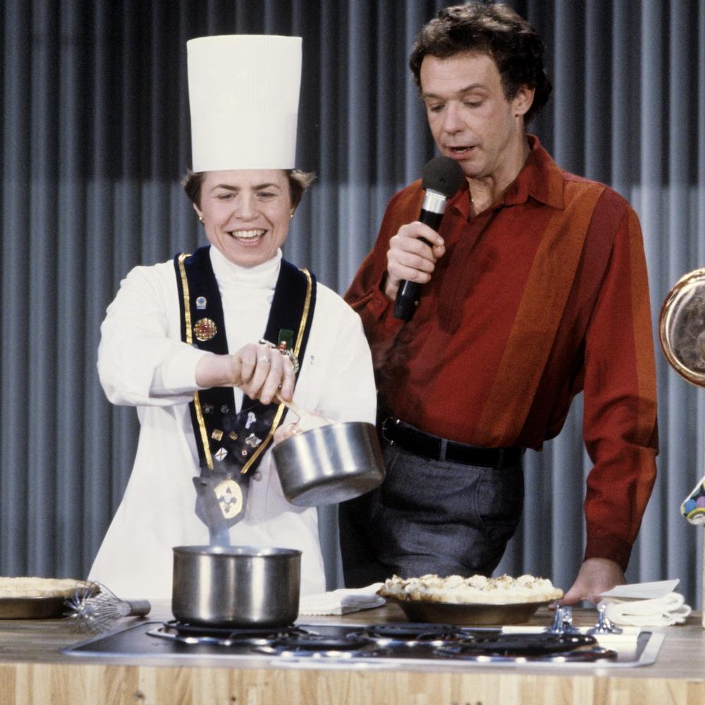 Sœur Angèle, qui porte la toque de chef, prépare une recette en compagnie de Jacques Boulanger.