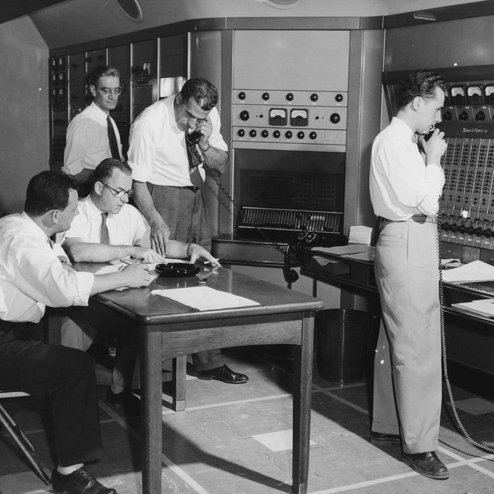 Des hommes consultant leurs notes à un bureau discutant au téléphone devant le large moniteur de la régie.
