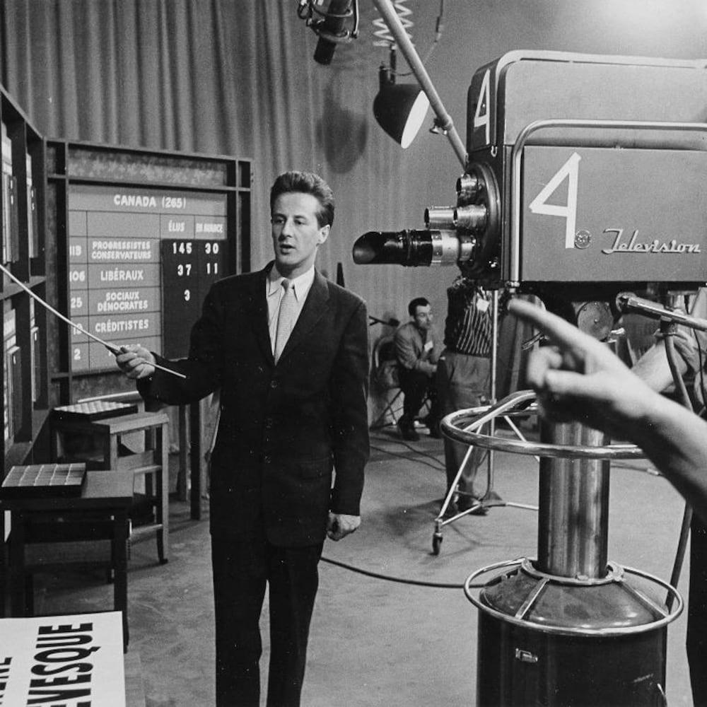 Le journaliste Pierre Paquette pointant un tableau d'une baguette devant un caméraman.