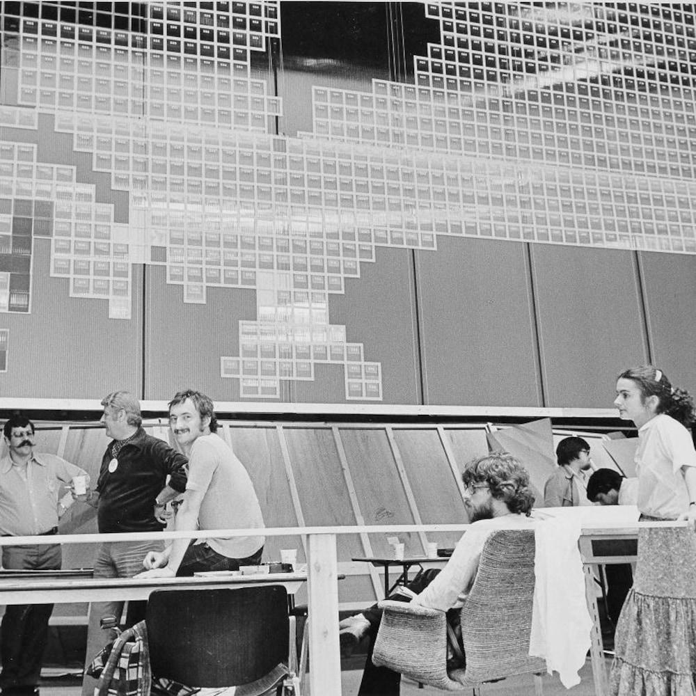 Une dizaine d'employés sont postés à l'arrière de l'immense carte formée de petits carrés numérotés pour chaque circonscription.