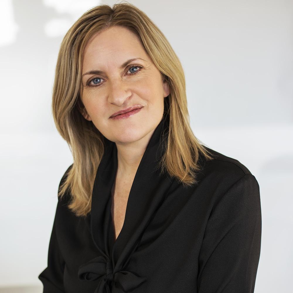 Une femme blanche, avec un chandail noir, est assise sur un banc et regarde droit dans l'objectif de la caméra.