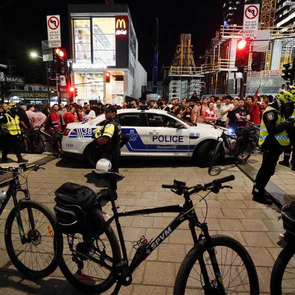 Des policiers du SPVM devant une foule au centre-fille.