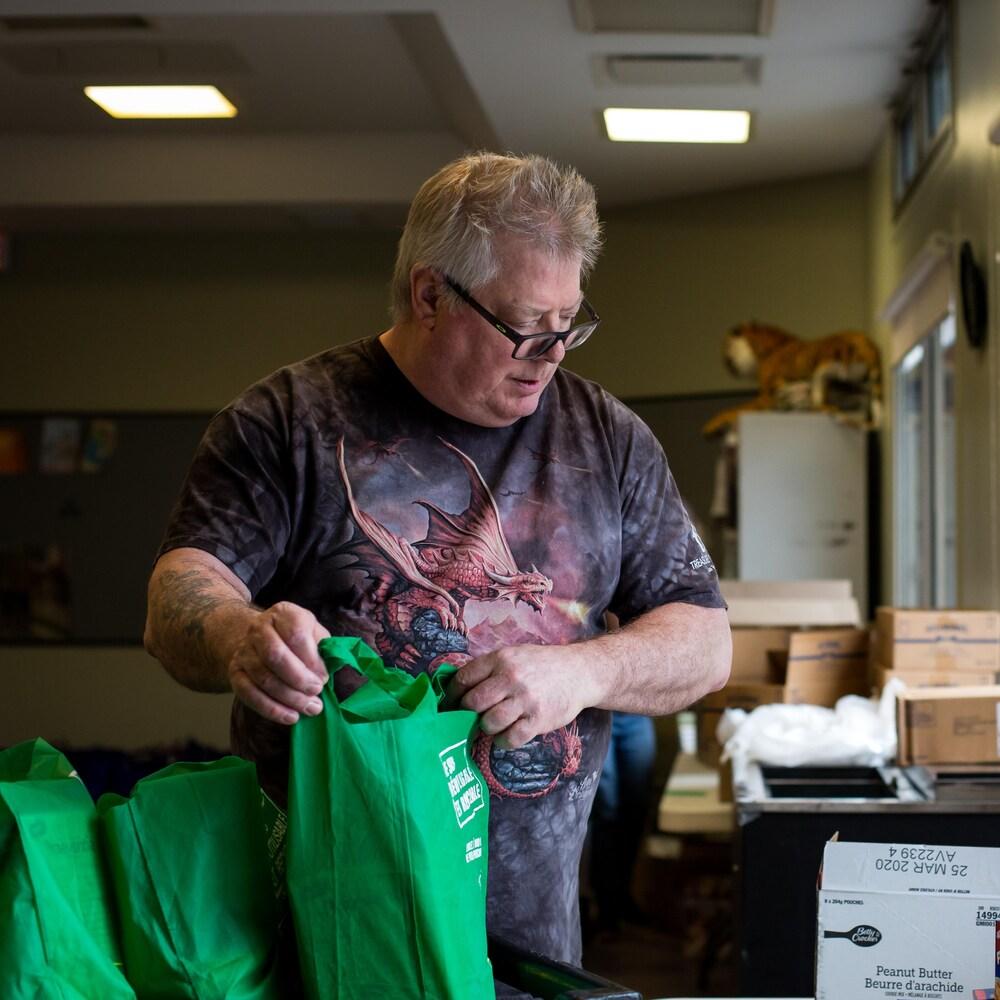 Jacques Schryburt remplit un sac avec des denrées.