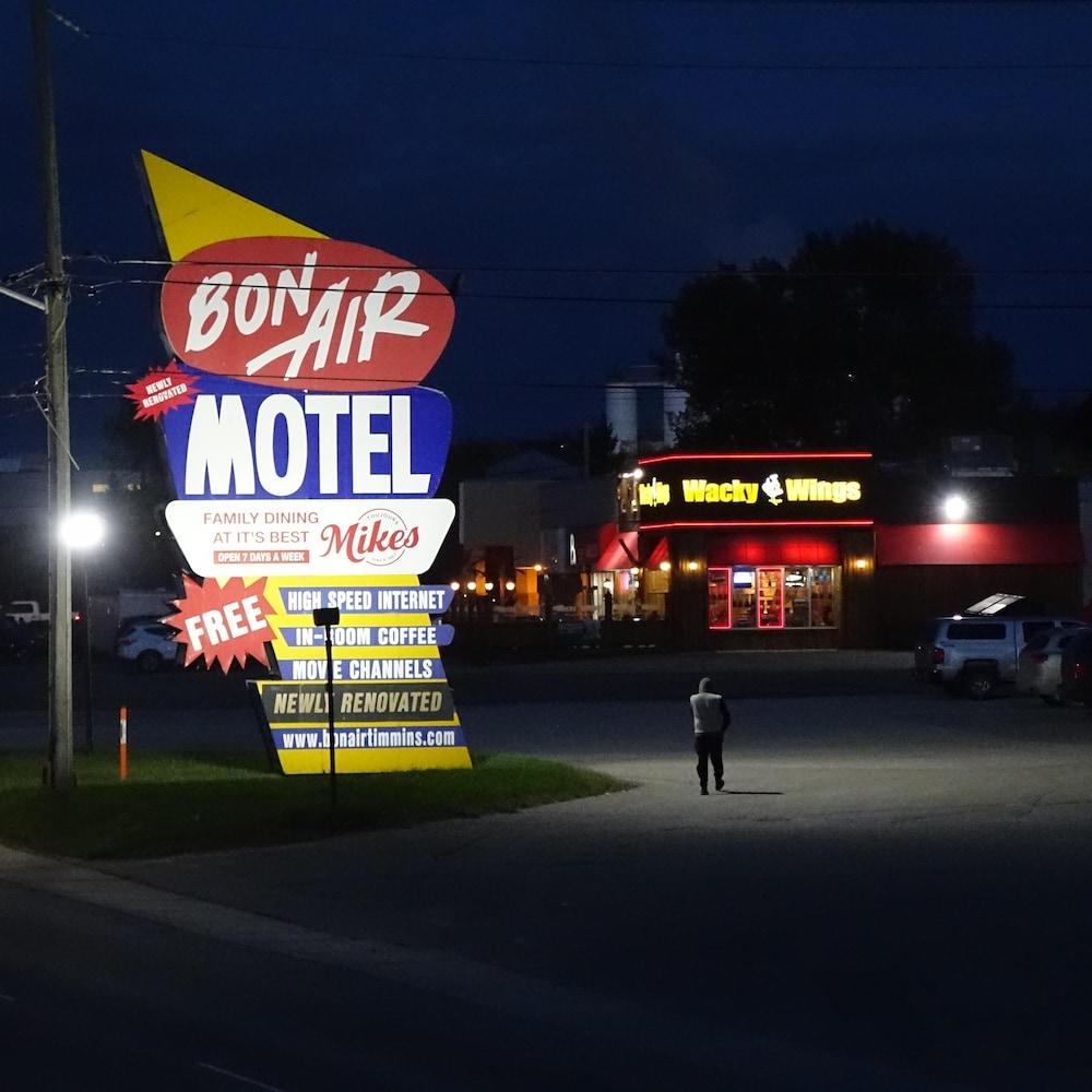 Un homme est visible par la lumière projetée d'un panneau de publicité.