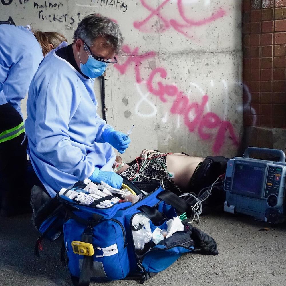 Deux ambulanciers à côté d'un jeune homme couché sur le sol.