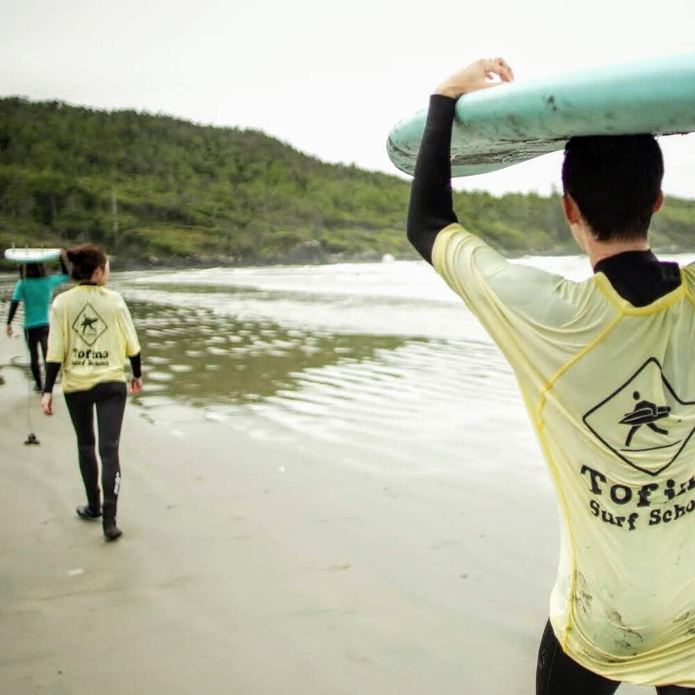 Des personnes portant des chandails de l'école de surf marchent sur la plage en tenant leur planche au-dessus de la tête.