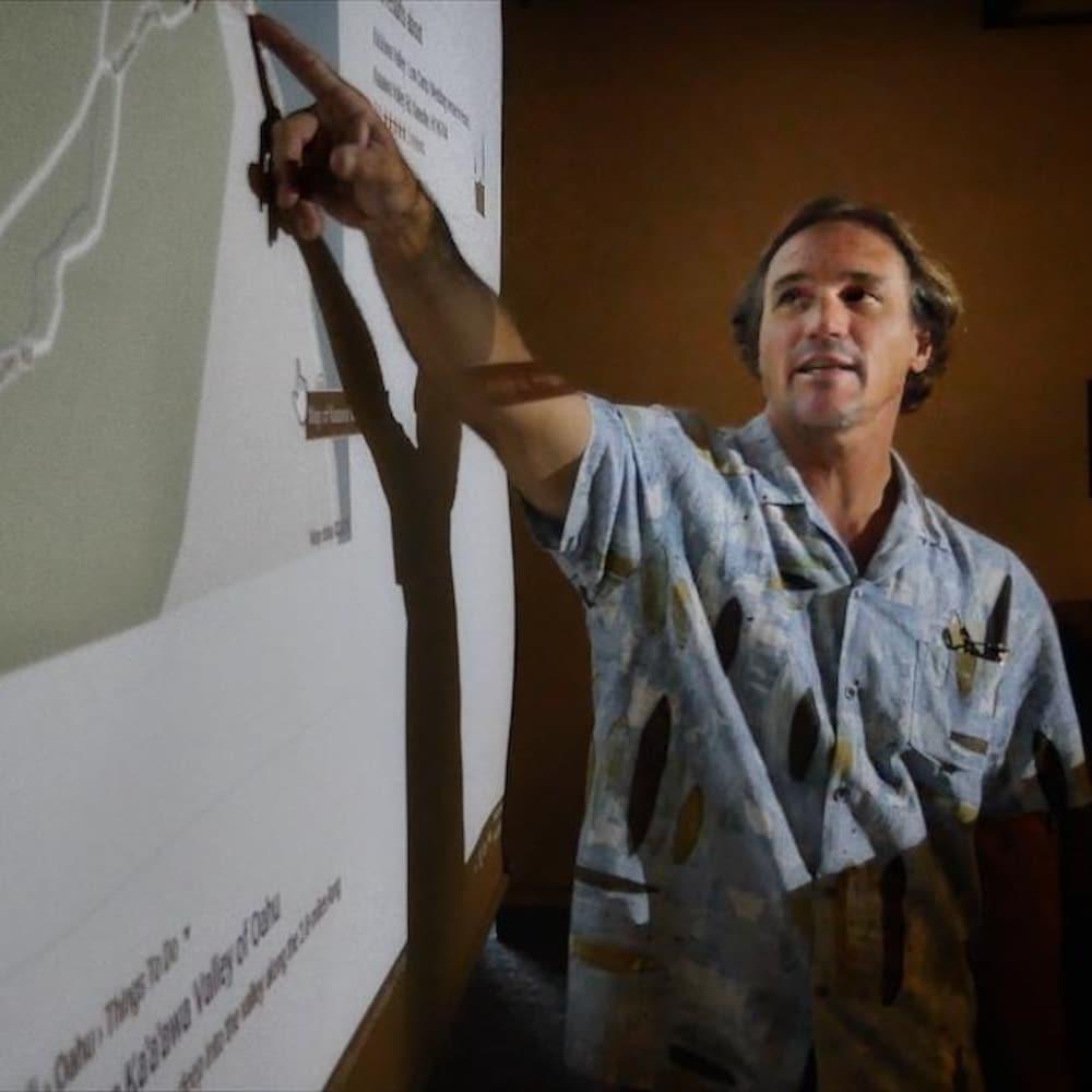 Ian Masterson en classe, montrant une carte sur un mur.