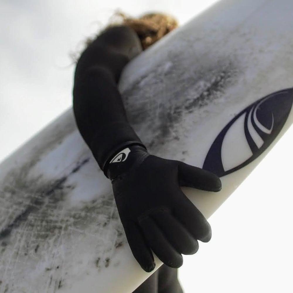 Une femme tient une planche de surf.