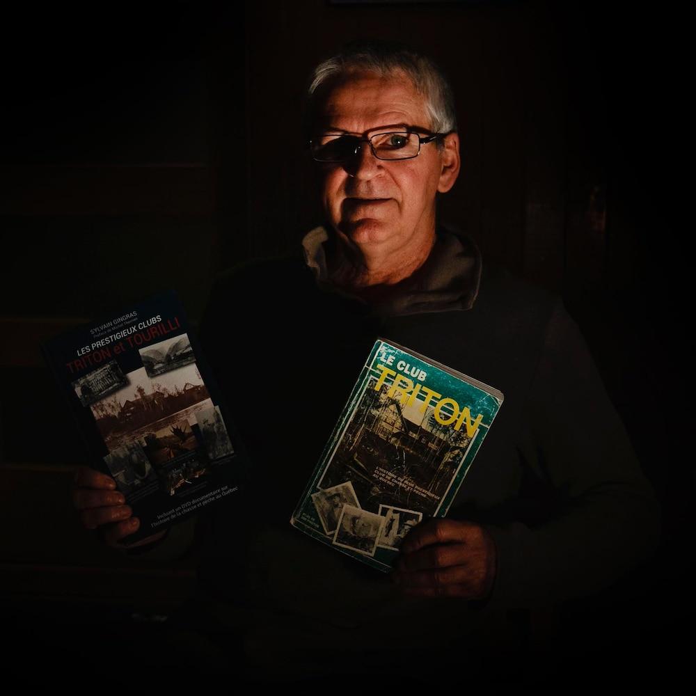 Sylvain Gingras pose pour la caméra avec les deux livres sur le club triton.