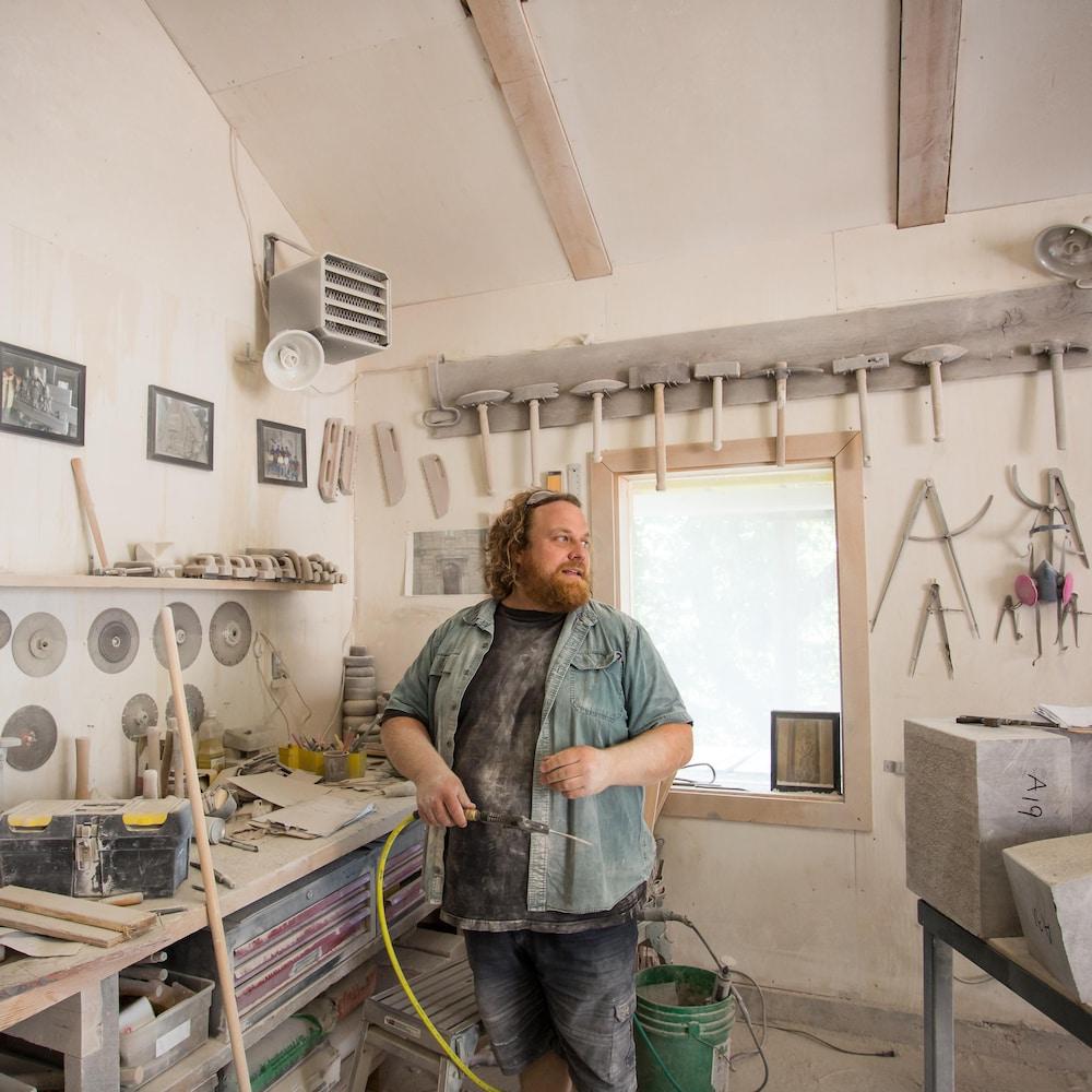 Adrien se tient à côté de son atelier, sur lequel se trouve plusieurs outils.