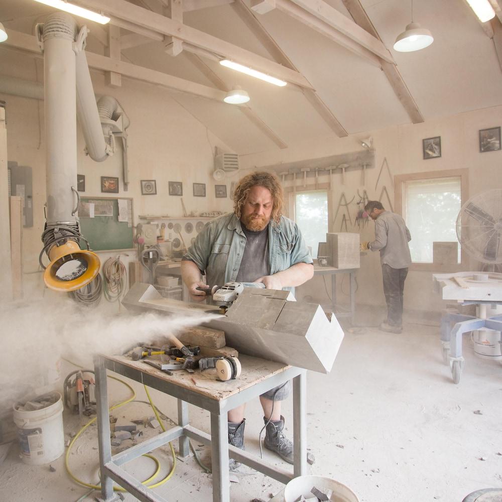 Le tailleur de pierre scie un morceau de pierre dans son atelier,  tandis qu'un long tube de dépoussiéreur est installé à ses côtés. Un collègue tailleur est à l'arrière.