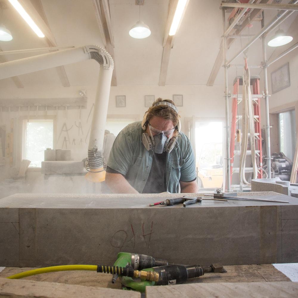 Adrien est penché sur une grosse pierre rectangulaire, dans son atelier poussiéreux.