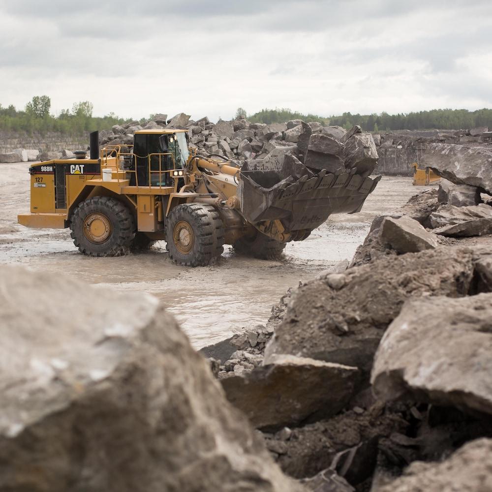 Un loader de marque CAT ramasse des gros morceaux de roche dans le fond de la carrière.