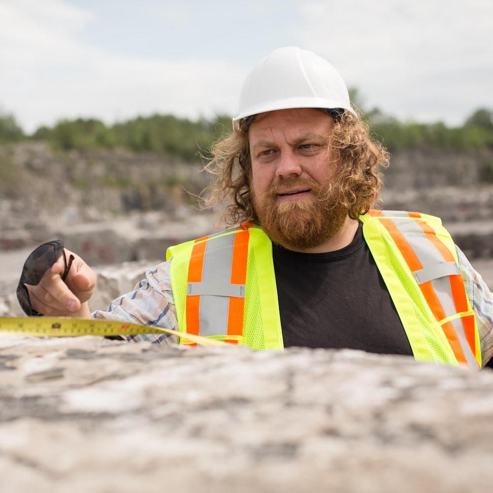 Adrien porte un casque et une veste de sécurité. Il mesure un bloc de pierre dans la carrière.