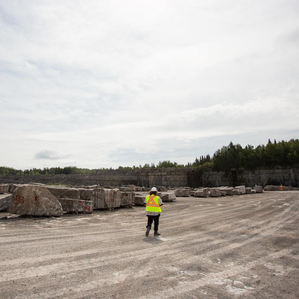 Adrien, vêtu de sa veste et de son casque de sécurité, marche dans le fond de la carrière, où des dizaines de blocs de pierre sont dispersés.