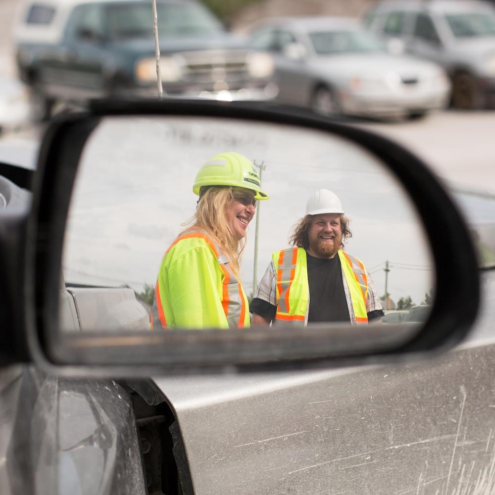 On aperçoit, dans le rétroviseur d'un véhicule, Céline et Adrien, souriants, lors d'une discussion dans le stationnement de la carrière.