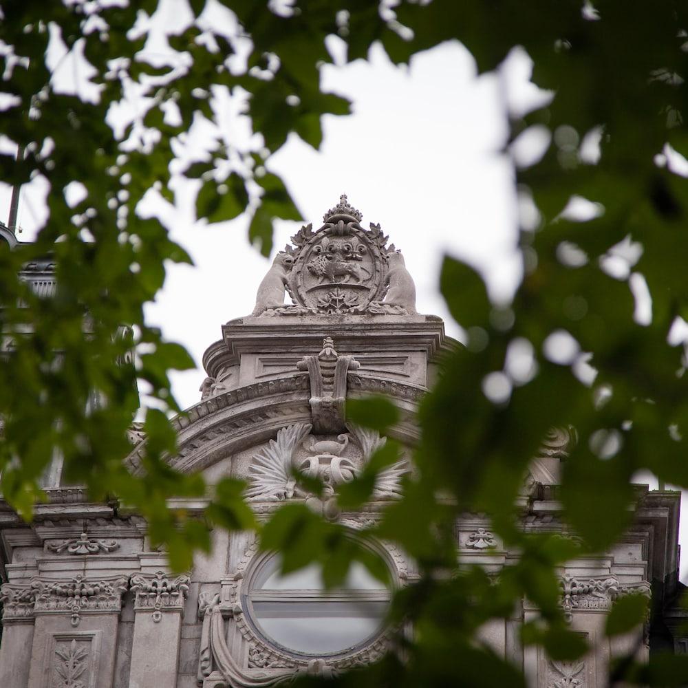 Une armoirie représentant deux castors est visible au sommet de l'assemblée nationale, au travers des feuillages des arbres.