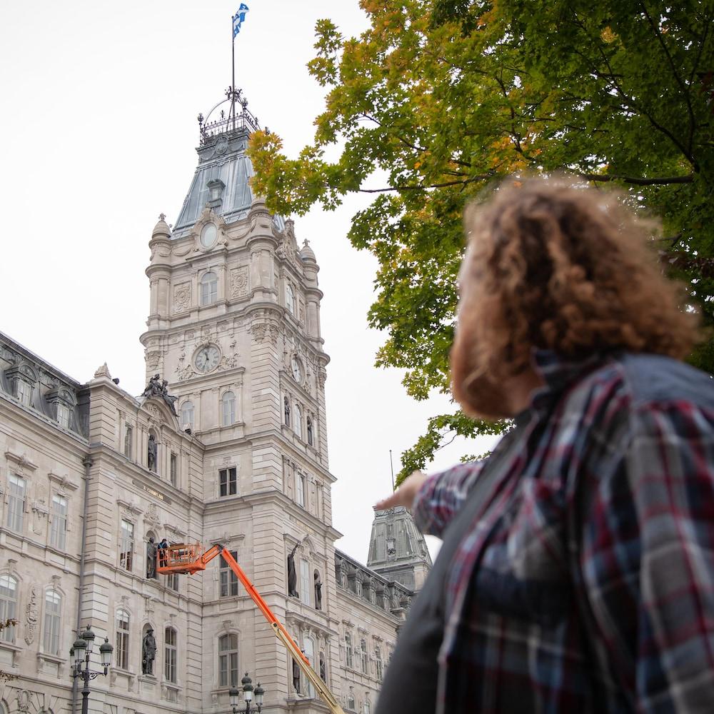 Adrien est debout, face au parlement. Il regarde la bâtisse en pointant certains éléments architecturaux.