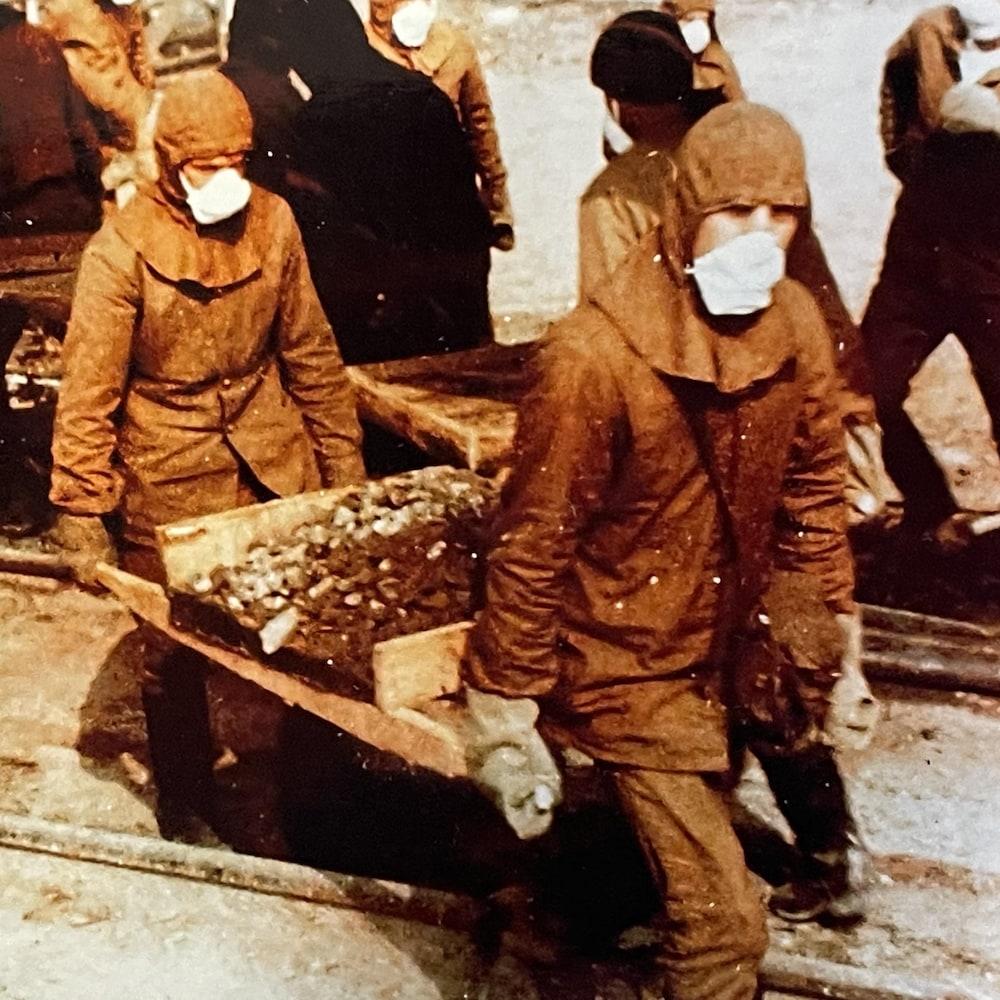 Des travailleurs déplacent une brouette.