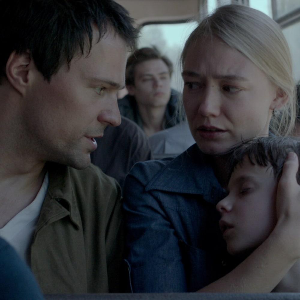 Un couple et un enfant réunis dans un véhicule de transport.