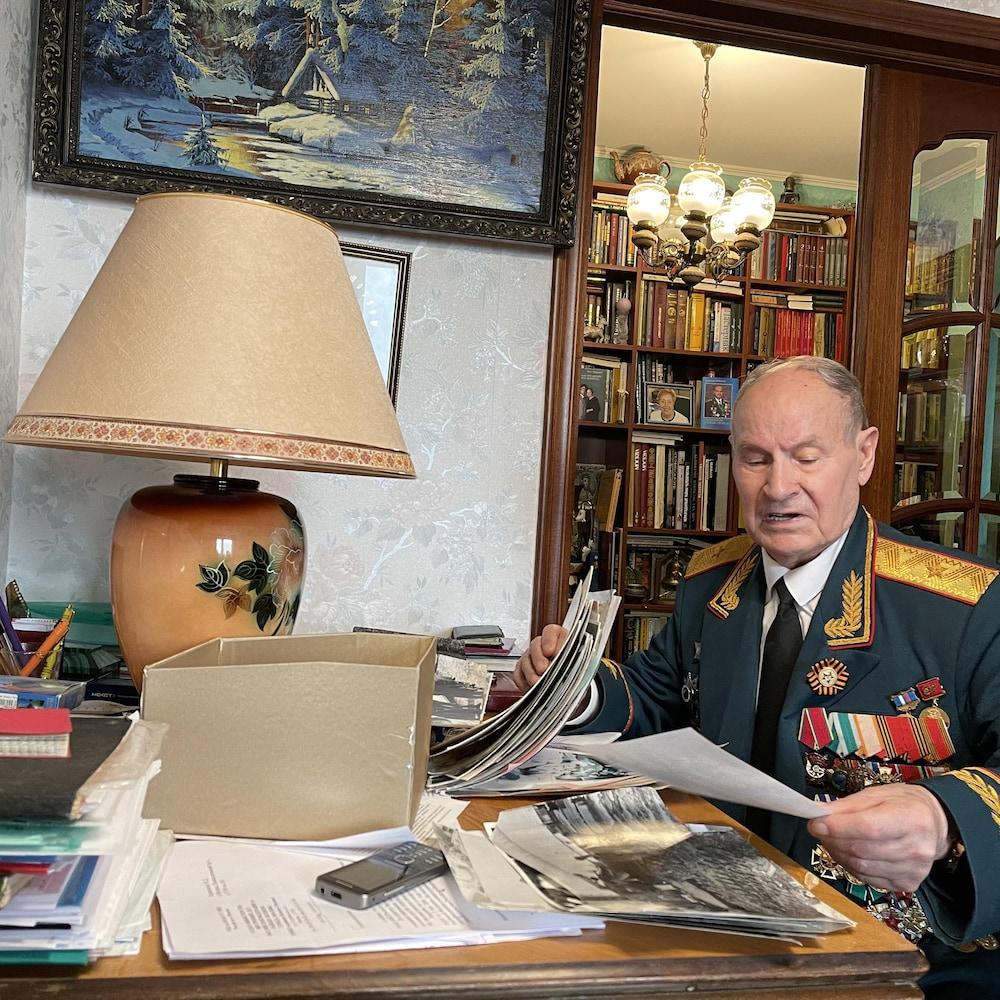 Le général Tarakanov assis à une table consulte des documents.