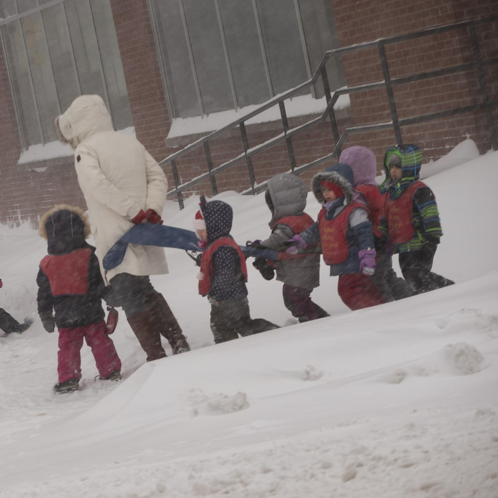Des enfants emmitouflés dans leurs manteaux suivent leur éducatrice sur le trottoir.