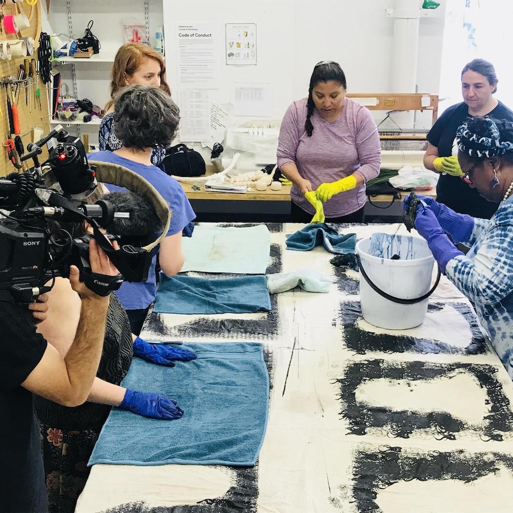 La femme qui essore un tissu s'appelle Carola Jones, c'est elle qui présente l'atelier. La robe qu'elle porte donne un aperçu de ses créations et de ce que les participantes vont faire à leur tour.