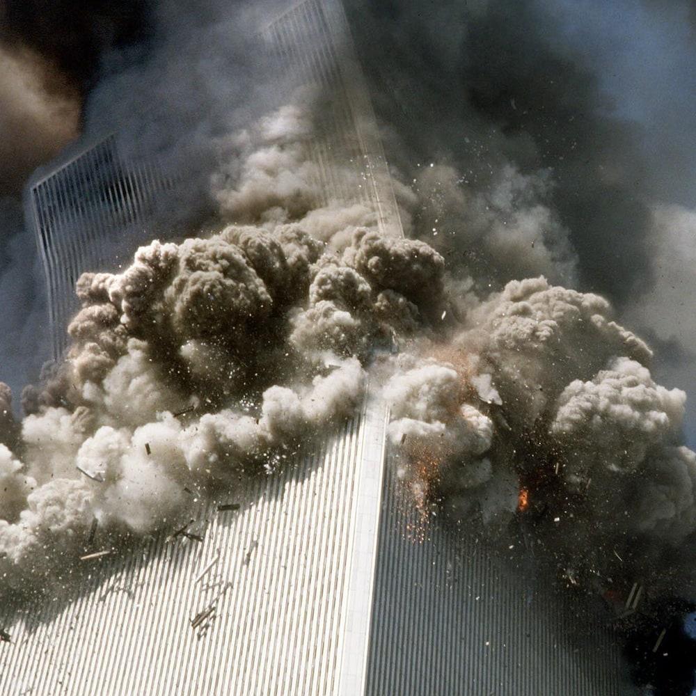 On voit en contre-plongée l'immeuble qui se rompt près de son sommet, la partie supérieure s'effondrant en position oblique,créant un immense nuage de fumée et de poussière.