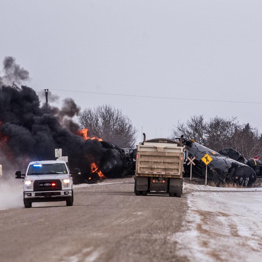 La scène du déraillement, avec de la fumée noire et des camions qui interviennent.