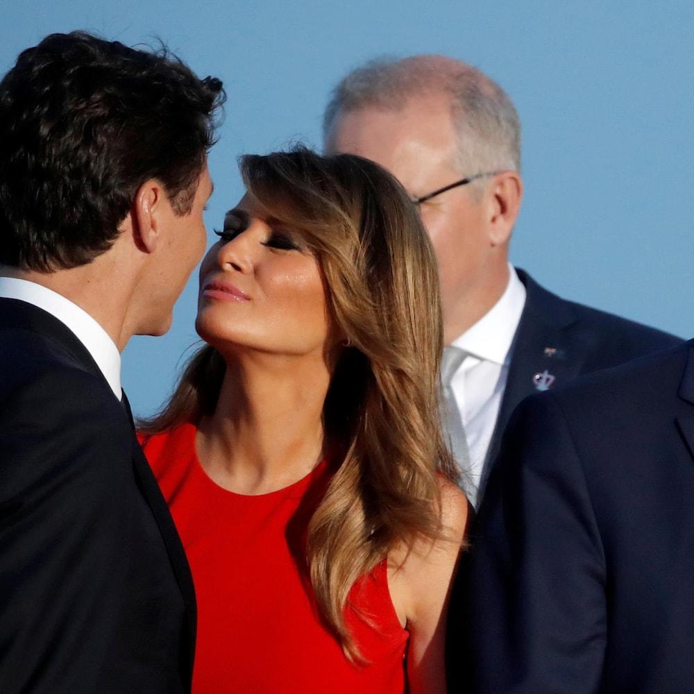 Justin Trudeau et Melania Trump s'embrassent sur les joues, alors que Donald Trump est à côté d'eux.