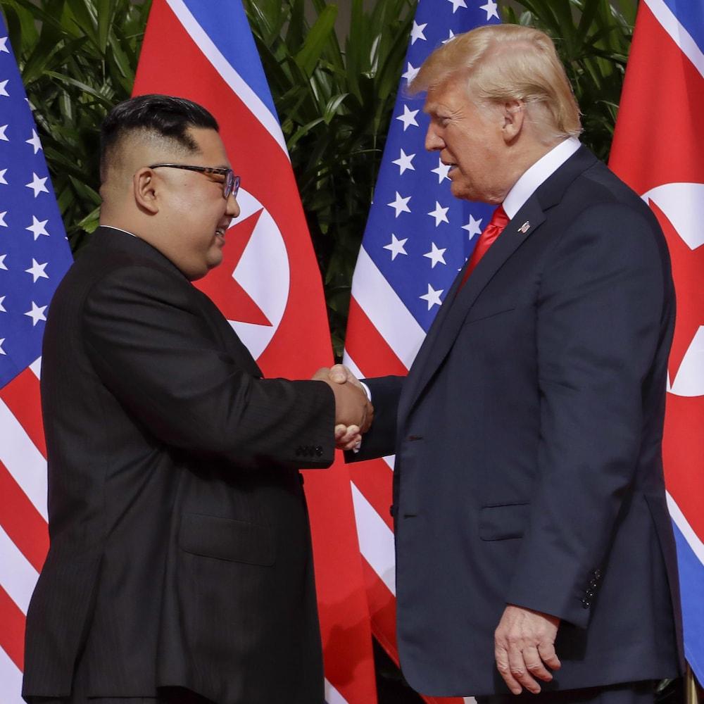 Donald Trump et Kim Jong-un se serrent la main devant des drapeaux.