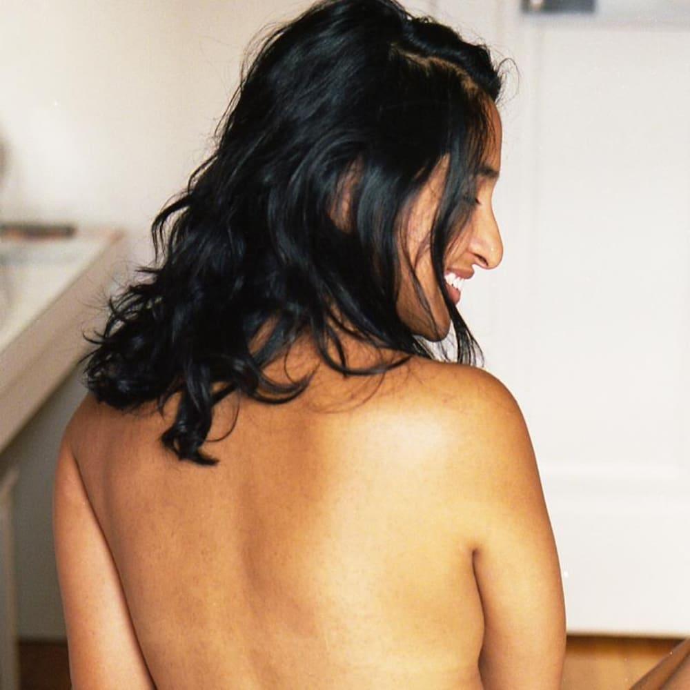 Une jeune femme assise sur un lit, sans soutien-gorge, regarde vers l'objectif.