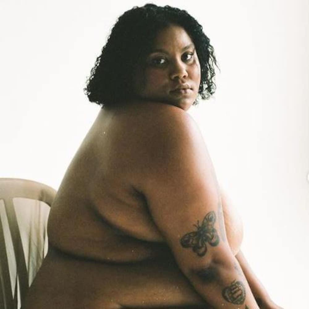 Une jeune femme noire, nue et assise sur une chaisse, est de côté. Elle est assise de côté, et tourne sa tête pour regarder droit dans l'objectif de la caméra.