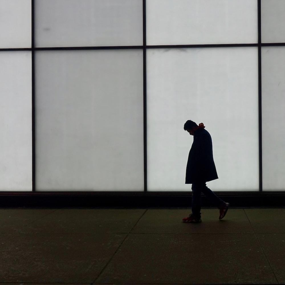 Un homme marche devant un mur lumineux.