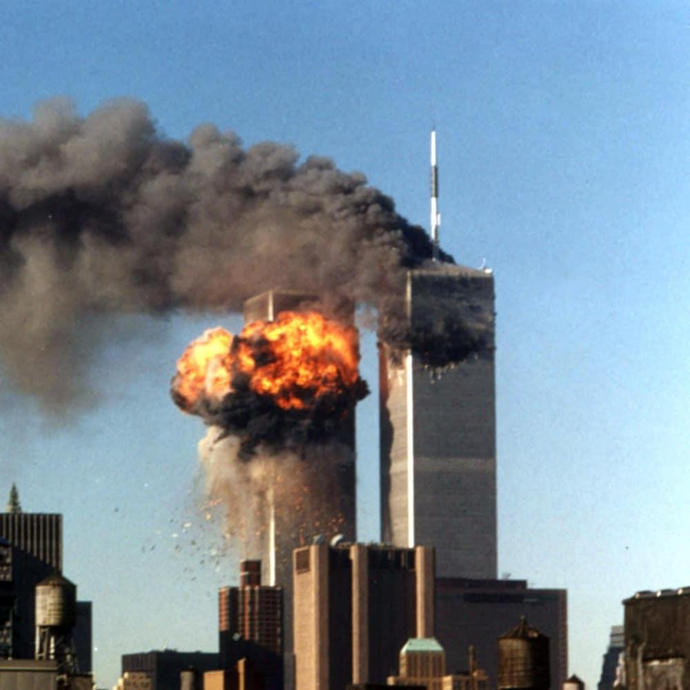 Une boule de feu s'échappe de la tour sud du World Trade Center, à New York, le 11septembre 2001. Le vol 175 de United Airlines a percuté la tour à 9 h 03, heure de l'Est, soit un peu plus de 15 minutes après que le vol 11 d'American Airlines eut percuté la tour nord, de laquelle s'échappe toujours un panache de fumée.