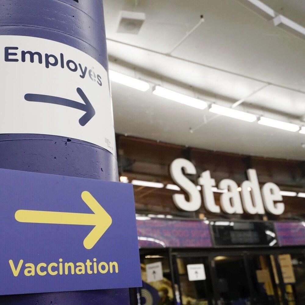 Une affiche indique la direction à suivre pour la vaccination au stade olympique.
