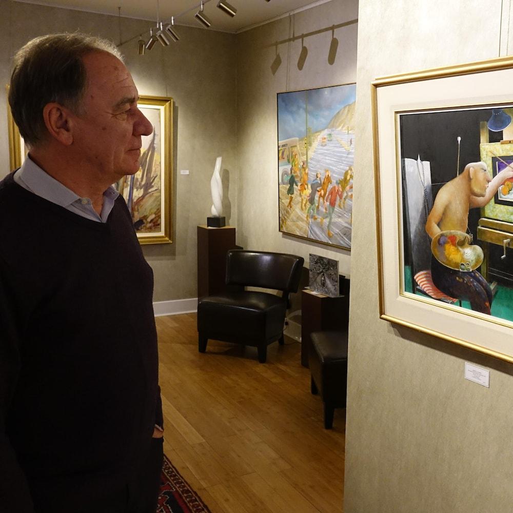 Jean-Pierre Valentin, dans sa galerie en train d'admirer « The Man who painted Oranges ».
